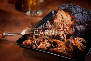 Close up Appetizing Pulled Pork on Black Tray with Fork on Top of Wooden Table.